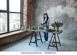 Putting Roses In A Vase Free Female In Gray Blouse And Jeans Make A Bouquet Over Gray