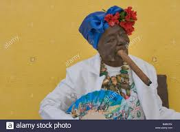 smoke fan for cigars older woman smoking a large cigar dressed in the white of santeria