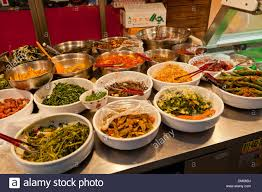 kimchi and other korean side dishes displayed for sale at