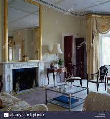large mirror above marble fireplace with club fender in