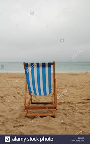 Chairs On A Beach An Empty Deck Chair On A Rainy Day At The Beach In Stock Photo