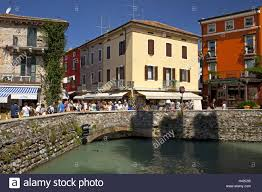 italy gardasee sirmione old town house facades tourists stock