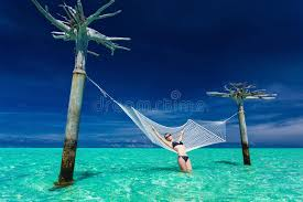 woman relaxing on over water hammock in the middle of tropical l