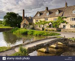 The Cotswolds Cottages by Cottages And Stone Bridge Lower Slaughter The Cotswolds Stock