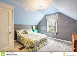 bedroom with vaulted ceiling and plank paneled walls stock photo
