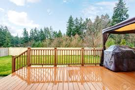 Grill Backyard by Backyard With Wet Deck Grill And Fence During Spring Stock Photo