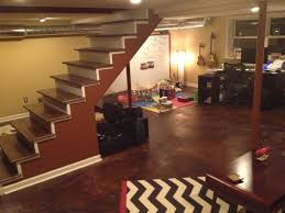 basement staircase with polished concrete flooring and area rug