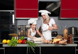 Cooks In The Kitchen by Two Little Girls In Clothes Cooks In The Kitchen At The Table With