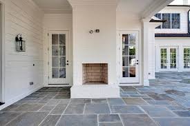 fantastic covered patio features a white brick outdoor fireplace