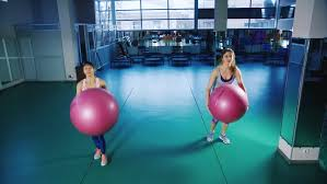 two attractive doing exercise with big balls stock footage