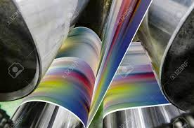 a large offset printing press running a long roll off paper over