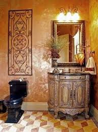 tuscan bathroom design with black toilet and wrought iron wall