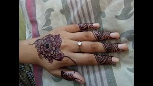 indian mehndi tikki design on back hand with henna applicator