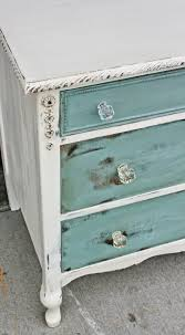 antiqued white with sea blue drawers distressed i love the glass