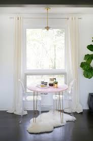 breakfast nook design with romantic style and two acrylic chairs breakfast nook design with romantic style and two acrylic chairs and round pink table with fur rug and sliding glass window with white curtains and corner