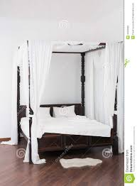 wooden canopy bed and a white hide on the floor stock photography