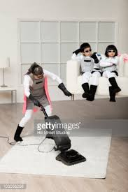 to vacuum low section of girl cleaning floor with vacuum cleaner at home stock