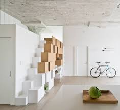 creative storage wall incorporates stairwell to new mezzanine