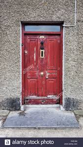 a distressed red door with peeling paint in an old house