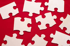 free puzzle piece template image of scattered white puzzle pieces on a red background overhead view of a group of differently shaped scattered white puzzle pieces on a red background