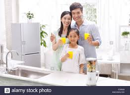 family drinking juice in kitchen stock photo royalty free image