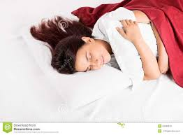 a sleeping on a bed hugging a pillow stock photo image