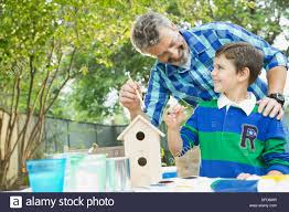 happy grandson and grandfather painting birdhouse in backyard