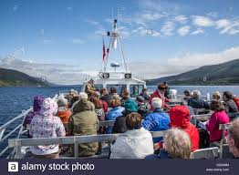 tourists on loch ness cruise boat in highlands of scotland stock