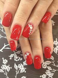 red polish with swarovski crystal ring finger over acrylic nails
