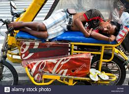 philippines tricycle driver sleeping on his tricycle in manila philippines stock photo