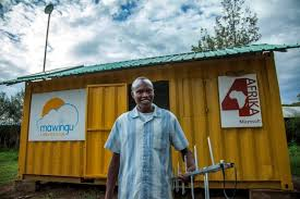 Benson Maina holds a TV white spaces antenna in front of the Mawingu White Spaces Broadband Microsoft