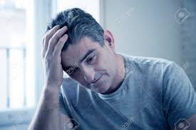 grey hair in 40 s 40s or 50s sad and worried man with grey hair sitting at home