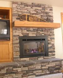 grey stack stone fireplace with brown wooden mantel shelf and