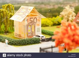 a euro bill house in a green neighborhood scenery stock photo