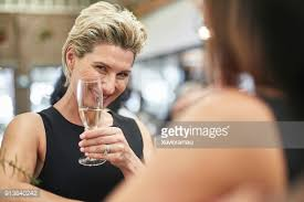 elegant mature woman elegant mature woman enjoying a drink after work stock photo getty