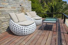 white outdoor furniture round rattan armchairs and glass table