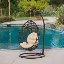 outdoor egg chair hanging on wooden platform near the pool outdoor