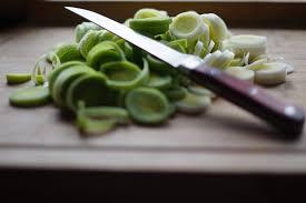 cuisiner les verts de poireaux légumes verts poireaux découpés en rondelle et couteau de cuisine