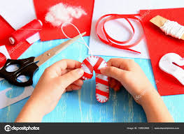 small child holds christmas felt candy cane in his hands sewing
