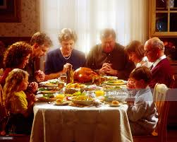 family praying together thanksgiving dinner stock photo