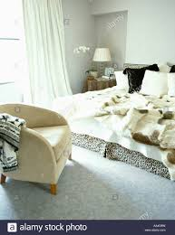 Faux Fur Bed Throw Cream Suede Armchair In Bedroom With Faux Fur Throws On Bed Stock