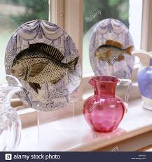 ornamental plates and jugs on windowsill display stock photo