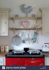 country kitchen with red aga oven cream paintedwall shelves with