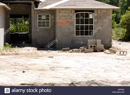 cement block house under construction on a sand base stock photo