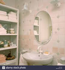 oval mirror on pink and white tiled wall above basin in small