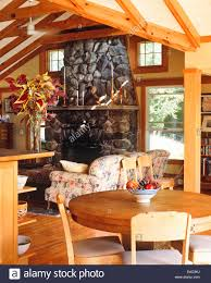 country house style living room with table couch and fireplace