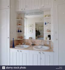 shelves on either side of mirror above double basins in white