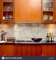 wok pan on hob in modern kitchen with wooden units and marble
