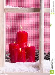 indoor christmas window sill decoration four red candles snow