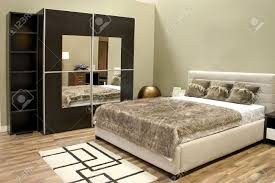 warm bedroom with wardrobe and large bed with pillows stock photo